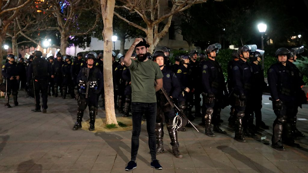 "Self-proclaimed postmodern social justice warrior David ""Riddle Me"" Shoreston seen here trying to disrupt fascist police officers with his trademark skinny jeans and fedora."